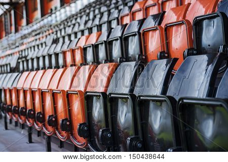 Rows of black and red plastic stadium seats depth of field concept