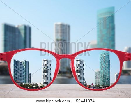 High buildings near the river focused in red glasses lenses