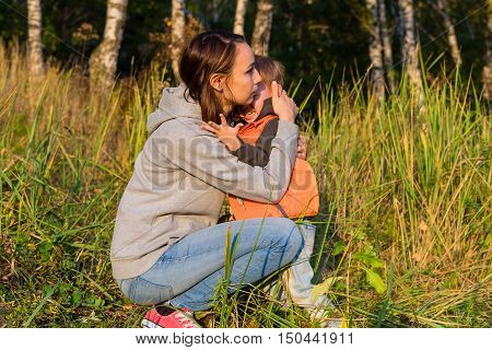 Mom hugging her son soothe a crying baby. Small boy crying in the arms of her mother. The grass at the edge of an autumn forest