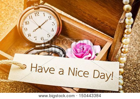 Have a nice day on paper tag with vintage pocket watch and rose in wooden box on wooden background.