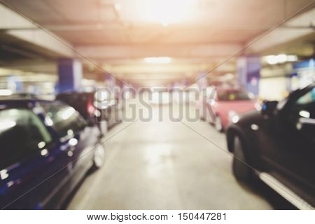 Blurred image of underground parking with cars.
