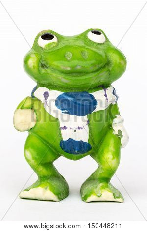 Statuette of a green frog close-up on a white background.