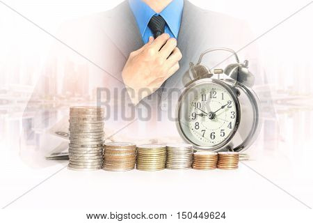 Double exposure of businessman in suit with a row of stack money coins and analog clock on the blurred cityscape background concept for business finances and saving money.