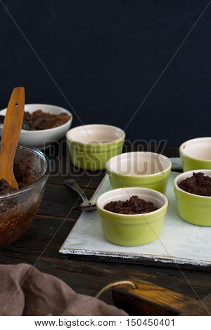 Ceramic bakeware with dough for the preparation of chocolate dessert on dark wooden table with copy space