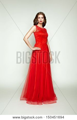 Fashion portrait of beautiful woman in elegant red dress. Girl with elegant hairstyle and jewelry