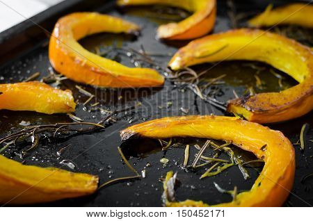 Freshly baked and juicy slices of pumpkin with addition aromatic herbs and olive oil on a baking tray. Pumpkin slices arranged on rows. Thanksgiving Halloween holidays concept. Selective focus.