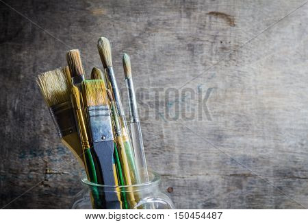 Paintbrushes of artist in a glass jar.