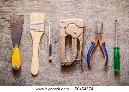 Brush trowel cutter stapler pliers and screwdriver on wooden table.