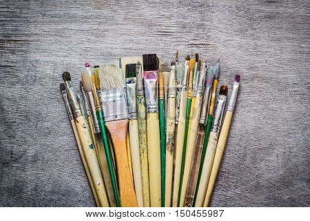 Paintbrushes of acrylic and oil colors on old wooden table.