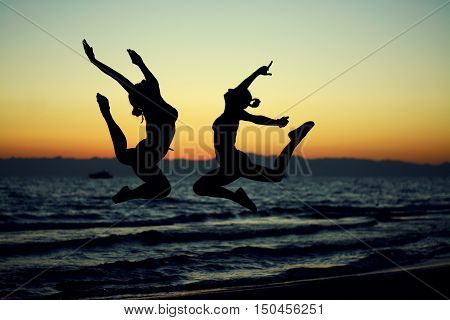 Silhouettes of dancers on a background of sea sunset. Choreography elements.