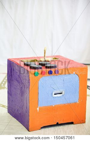 Do-it-yourself kitchen stove made from paper box and other trash. Imaginative and creative playing and creation educational approach concept.