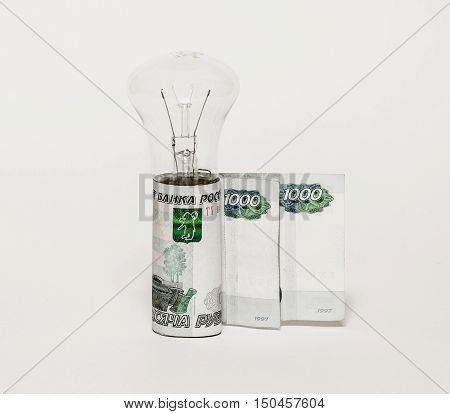 The electric incandescent lamp and euro notes on a yellow backgr