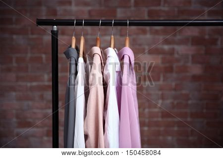 Hangers with female shirts on clothes rail against brick wall background