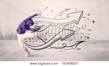A beautiful young hip hop dancer dancing contemporary street dance in front of urban grey wall background with lines and arrows concept