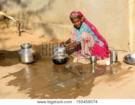 BHUJ RAN OF KUCH INDIA - JANUARY 13: The tribal woman in the village on the desert in the Gujarat state he is washing dishes by the route Bhuj in January 13 2015