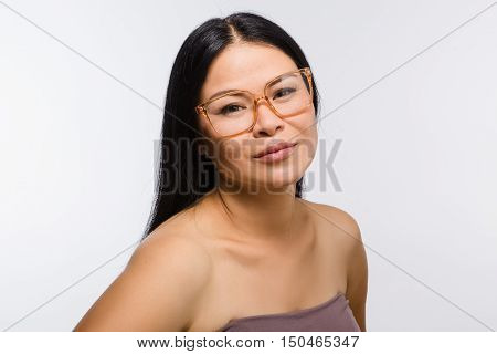 Picture of beautiful Korean or Asian woman or lady in glasses in studio. Happy woman demonstrating fashionable glasses for photographer.