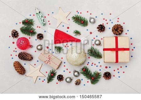 Christmas background of gift box, fir tree, conifer cone and holiday decorations on white desk top view. Flat lay styling.