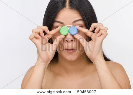 Pretty brunette woman holding contact lenses container or case in front of her isolated on white background in studio.
