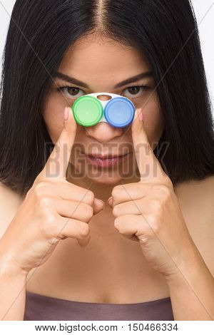 Picture of attractive woman with container for contact lenses. Korean or Asian lady looking at camera while holding case for contat lenses in studio.