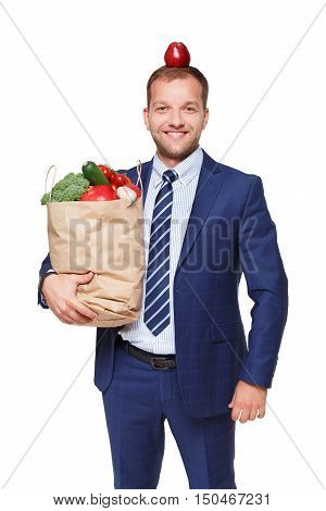 Handsome young businessman in suit holds shopping bag full of groceries with apple on head, isolated at white background. Healthy food shopping. Paper pack with vegetables and fruits, happy buyer.