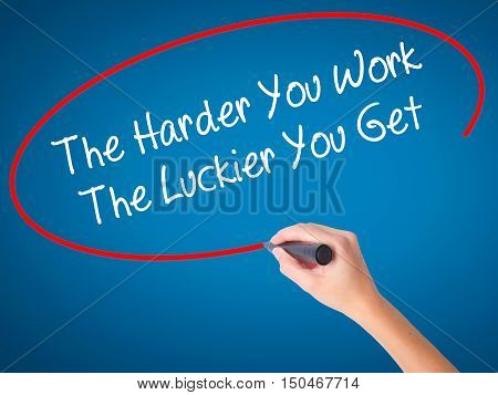 Women Hand Writing The Harder You Work The Luckier You Get  With Black Marker On Visual Screen