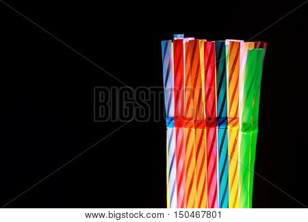 Colorful drinking straws on black background .
