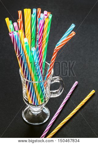Colorful drinking straws in the glass on black background