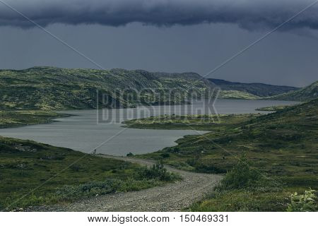 Approaching storm front in the highlands. A view of the green hills and the lake. Arctic summer the tundra Norway.