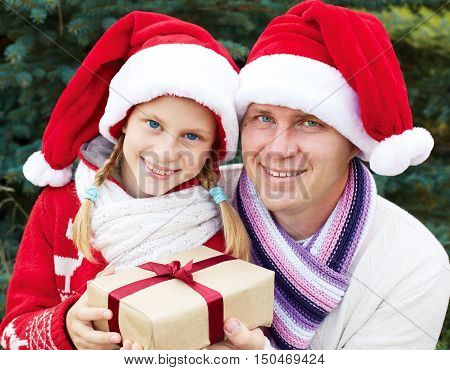 A child receives a Christmas gift. Portrait of a family at Christmas