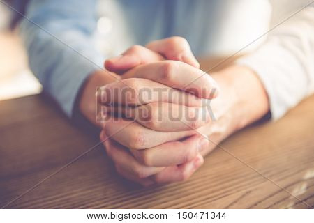 Cropped image of handsome businessman clasping hands together