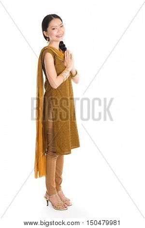 Young mixed race Indian Chinese girl in traditional punjabi dress greeting, full length standing isolated on white background.