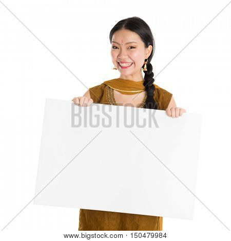 Portrait of young mixed race Indian Chinese female in traditional punjabi dress holding a blank white paper card, standing isolated on white background.
