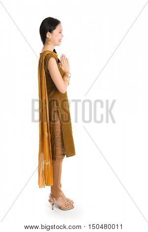 Side view of young mixed race Indian Chinese girl in traditional punjabi dress greeting, full length standing isolated on white background.