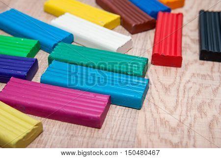 set of colorful plasticine blocks on wooden desk
