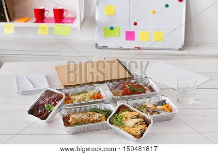 Healthy daily ratio for diet, foil boxes of meat and vegetables with water glass on working table in office. Workspace and healthy food nutrition