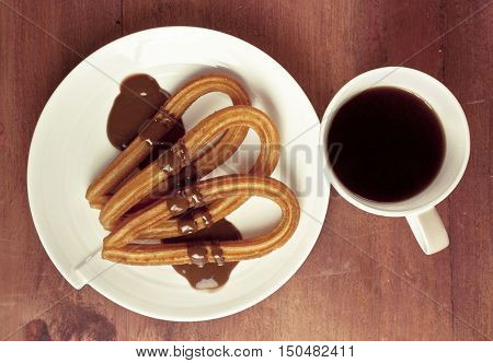 A closeup photo of churros with chocolate, traditional Spanish, especially Madrid, dessert, particularly for Sunday breakfast. On wooden background, shot from above. With a cup of black coffee