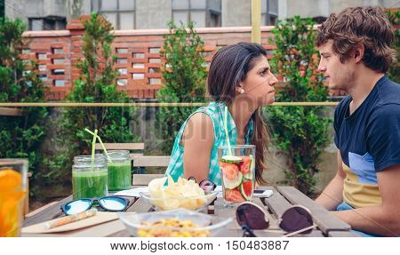 Serious woman arguing with young man sitting behind of table with healthy drinks and snacks in a summer day outdoors