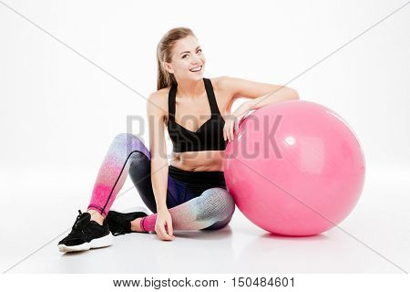 Young beautiful fitness girl with pink ball sitting and looking at camera isolated on white background
