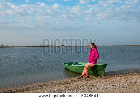 Dreaming woman relaxes near small boat on the beach in the windy weather.