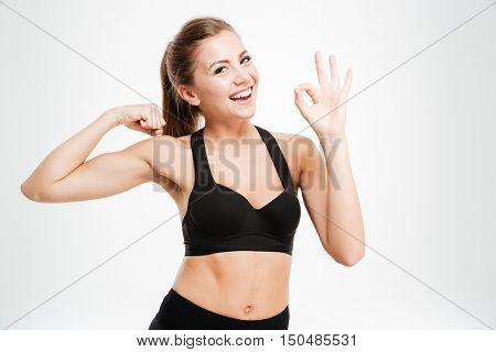 Smiling sporty woman showing ok sign with fingers isolated on a white background