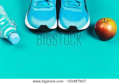 Blue sneakers, water and apple on blue background. Concept of healthy lifestile and food, everyday training and force of will.