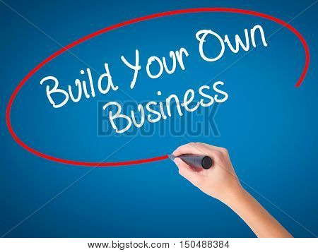 Women Hand Writing Build Your Own Business With Black Marker On Visual Screen.