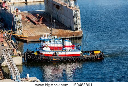A tugboat at an industrial pier in Tampa Bay