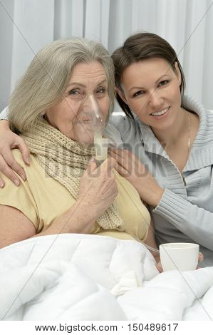 Senior ill woman with caring daughter at home