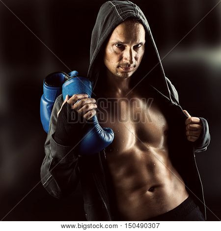 Serious Young muscular man boxer wearing jacket with hood. Boxing gloves slung over his shoulder on dark background indoor.