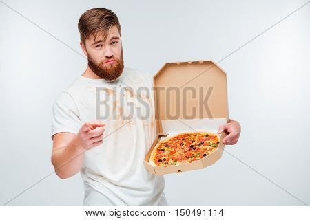 Confident bearded man holding pizza box and pointing at camera isolated on white background