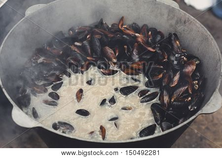 Fresh mussels grill in couldron pot. Seafood barbecue outdoors. Picnic healthy food, seafood in shells cooking at large metallic pan. Steamed and stewed shellfish, mediterranean cuisine