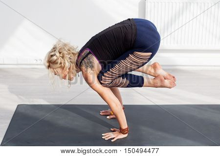 Blonde woman doing yoga handstand on the mat at the gym