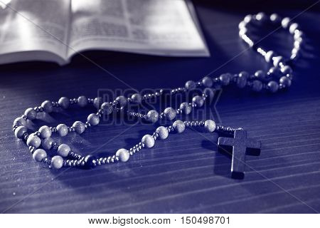 rosary and bible on the wooden table