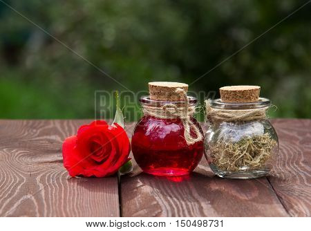 Rose Elixir and herbs for beauty and skin care. Natural cosmetics. Spa concept. Rose oil and aromatherapy. Love drink. Elixir of Love